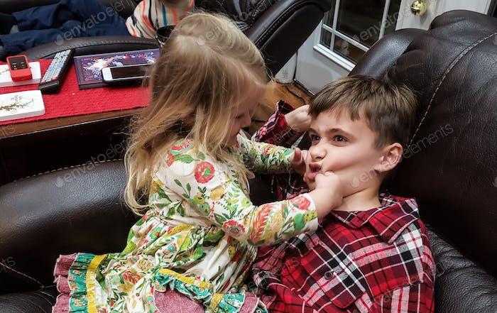 Pinching cousins in a chair.