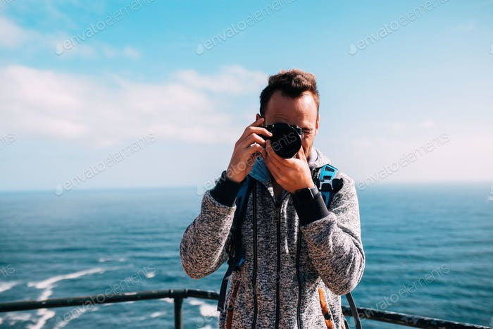 Young men snapping photos by the ocean