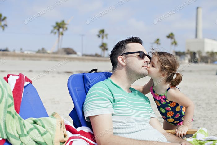 little caucasian girl in a bathing suit kisses dad's cheek