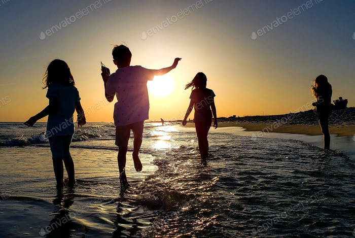 Three kids having fun dancing down the beach in the ocean hoping to splash a tourist on her cell