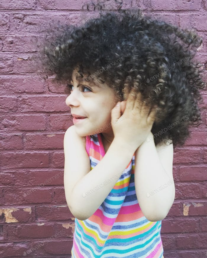 Model on brick wall- happy cute girl with curls