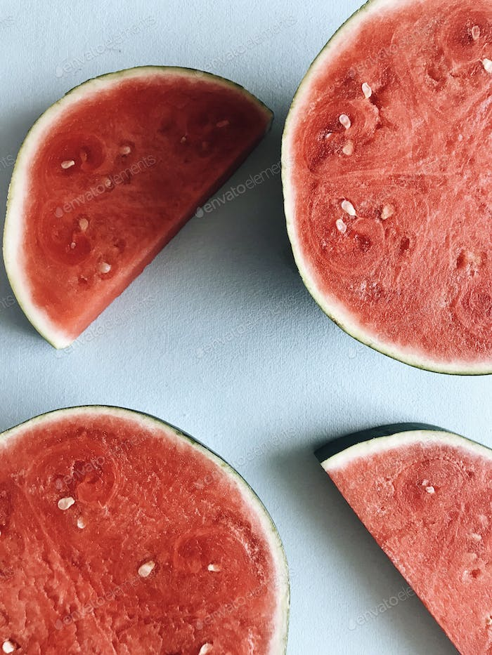 Slices of red watermelon on light blue background