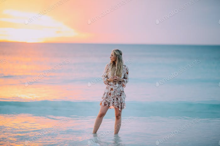 Schönes blondes Mädchen mit langen Haaren am Strand und beobachtet Sonnenuntergang