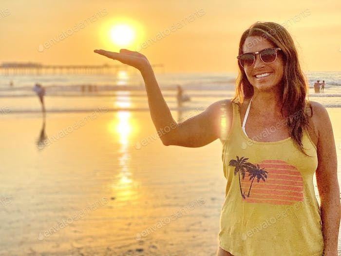 California girl having fun in the sun at the beach at sunset