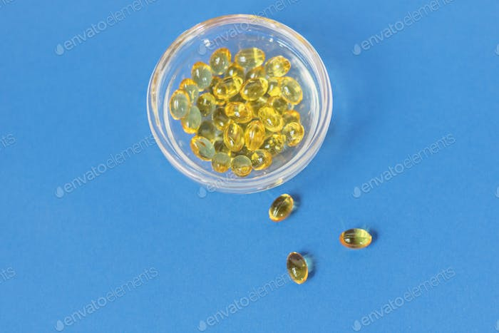 Yellow gelatin capsules with vitamin D3 in a glass container on a blue background.