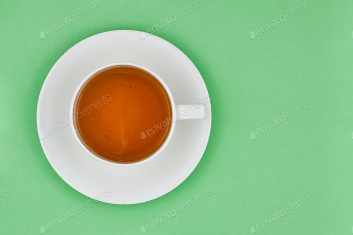 Cup of healthy green tea on a light green background