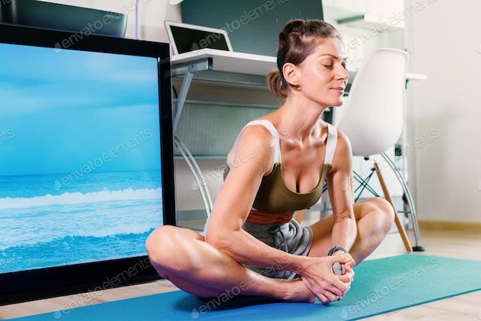 Mujer joven en forma haciendo ejercicio de estiramiento de yoga