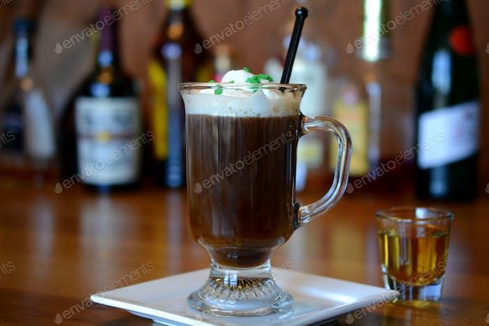 Irish Coffee cocktail Irish Whiskey in shot glass for St. Patty's Day on wooden bar liquor bottles