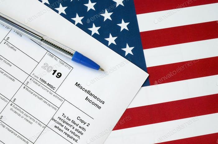 Formulario 1099-misc Ingresos diversos y pluma azul en la bandera de los Estados Unidos