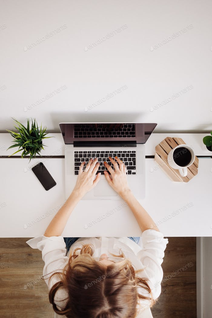 La mujer trabaja con el portátil. Escribiendo en el portátil. Escritorio de oficina en casa con ordenador portátil, teléfono sobre mesa blanca.