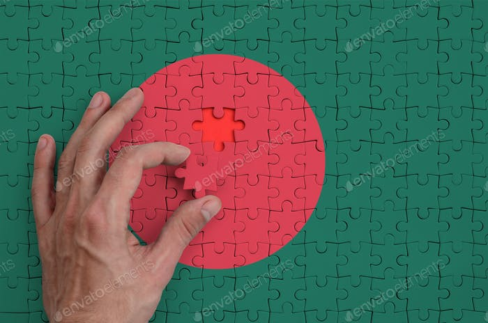 Bangladesh flag  is depicted on a puzzle, which the man's hand completes to fold.