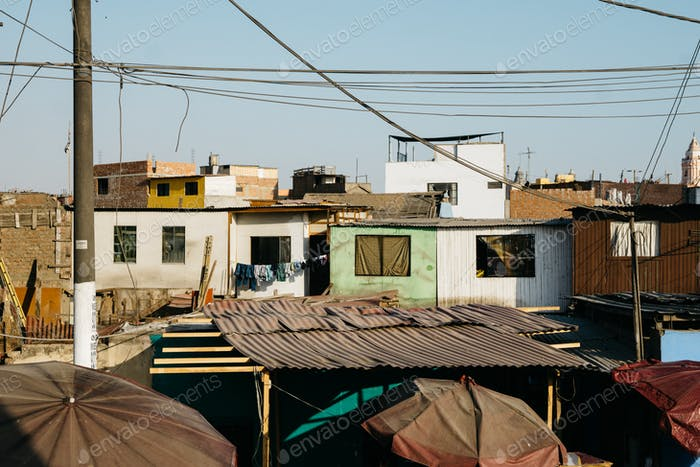 Sunset casting warm shadows and light against densely packed homes in a poor neighborhood in Lima