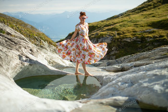 a girl by a river walks in her long floral dress. All women are princesses