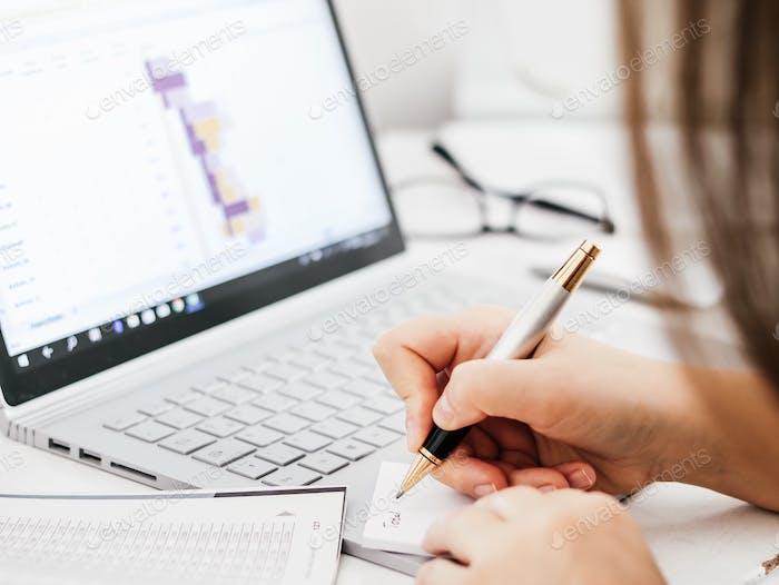 Mujer escribiendo. Teclado portátil. Gráfico. Contabilidad de pérdidas y ganancias. Finanzas