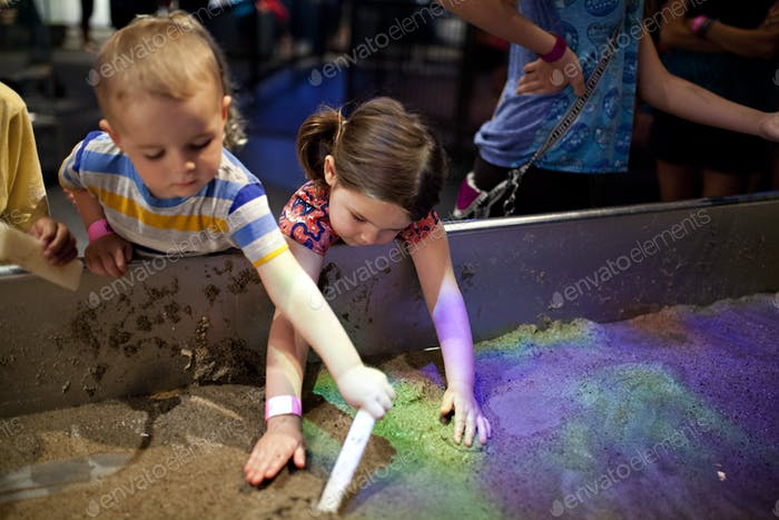 two kids working in a sand erosion tub at the museum.