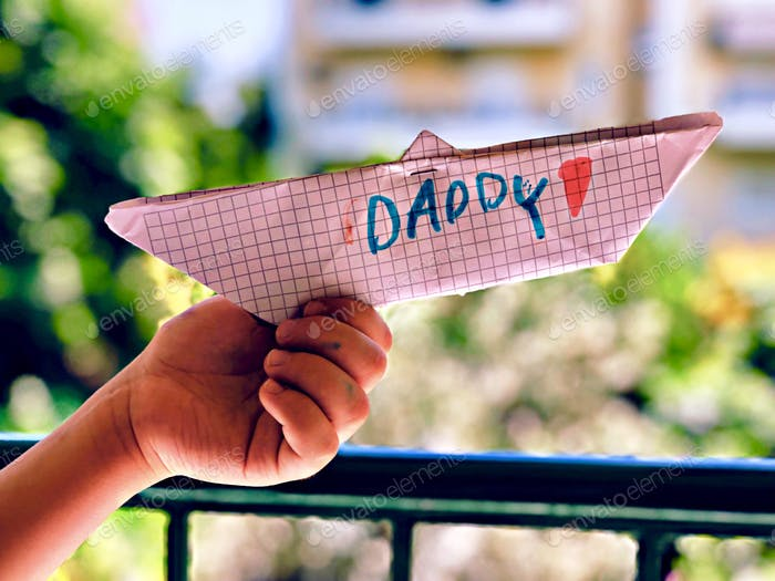Kid holding a paper boat as a gift for father's day...