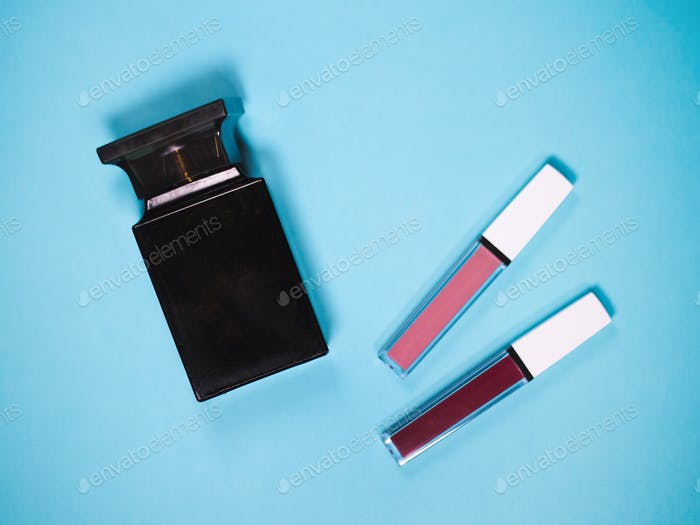beautiful beige and red lip glosses with perfume bottle, isolated on blue background.