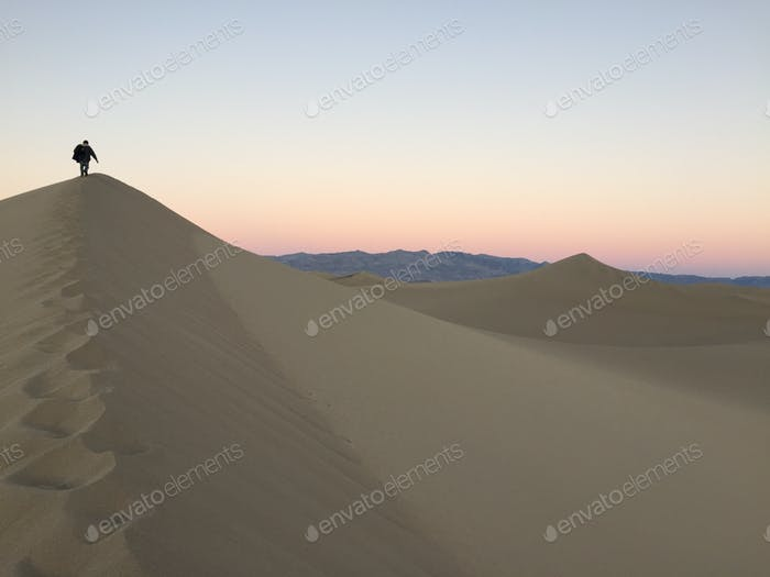 Solo hiker on Death Valley's Mesquite Dunes at sunset under the moonlight!