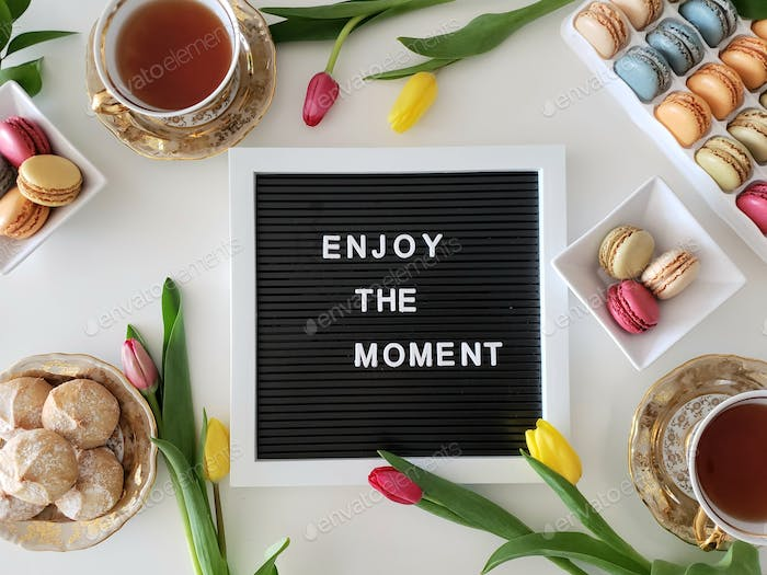 Positive message on letter board surrounded with colorful items, flat lay pastries and flowers