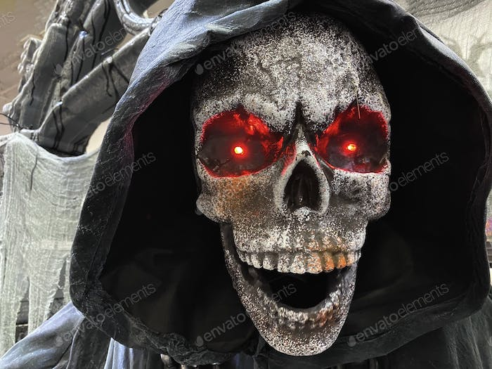 Scary ghoul skeleton hooded with glowing red eyes decoration for Halloween