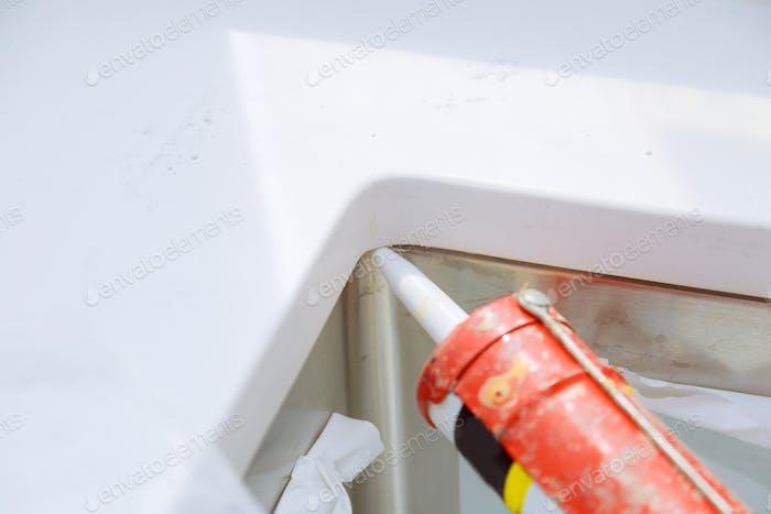 Worker installing granite sink in kitchen silicone sealant on granite countertops