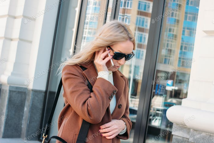 Stylish fashionable blonde woman wearing coat and sunglasses speaking on mobile phone at the street