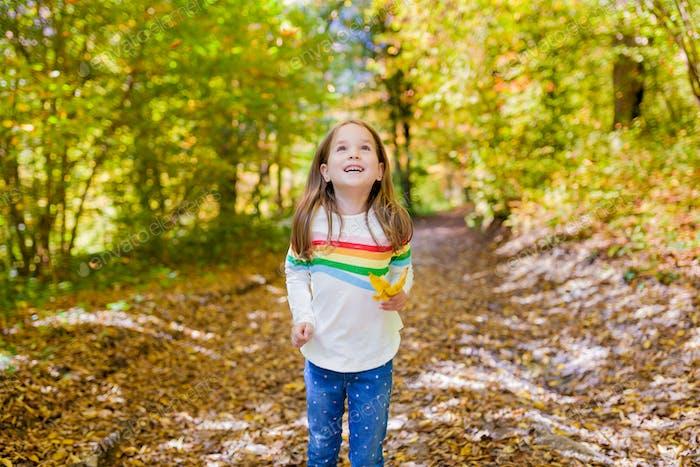 Erholung im Freien und tolle Abenteuer mit Kindern im Herbst. Ein kleines Mädchen geht durch die a