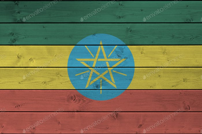 Ethiopia flag depicted in bright paint colors on old wooden wall close up