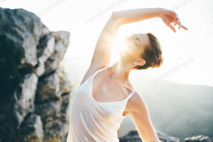 Young woman dancing at the mountain at sunset.