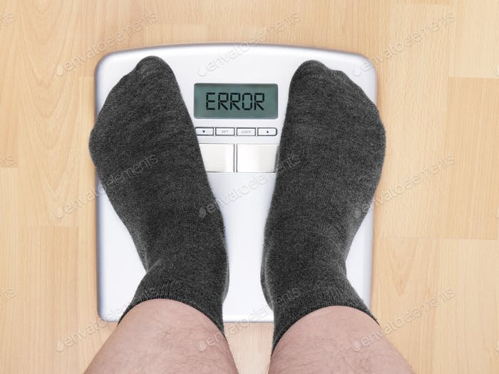 male feet standing on bathroom scales