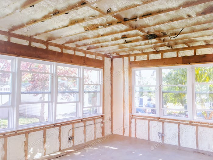 Light and bright room in home with many windows stripped down to studs and freshly spray foam