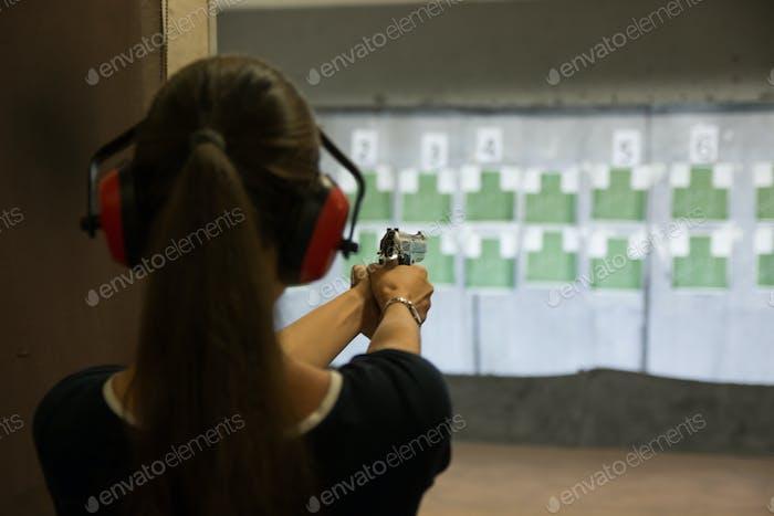 Woman aiming gun in shooting range