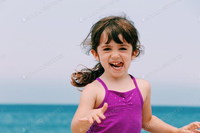 Little girl running on beach, making funny face