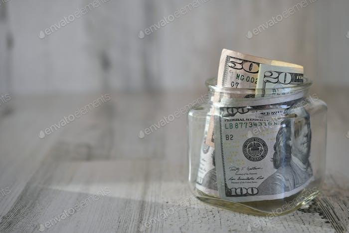 Dollars, money, currency, cash jar hundred dollar bills, salary, extra income, side hustle, earnings