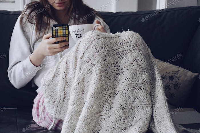 Young teenage girl sitting on a couch with a blanket, a cup that says BUT FIRST TEA and using her mo