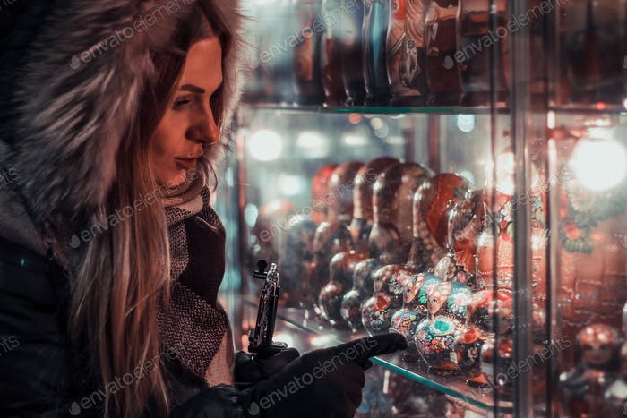 Girl is choosing souvenir matrioshka