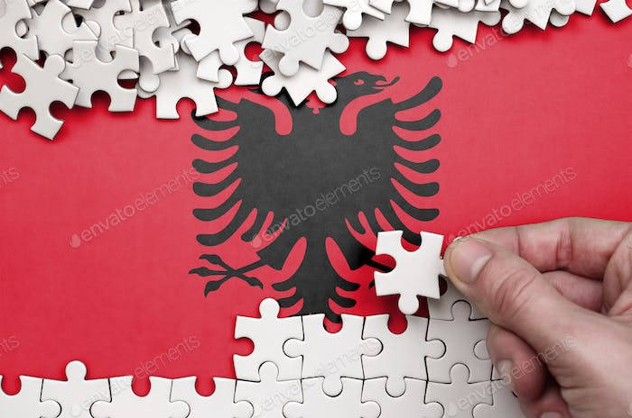 Albania flag  is depicted on a table on which the human hand folds a puzzle of white color.