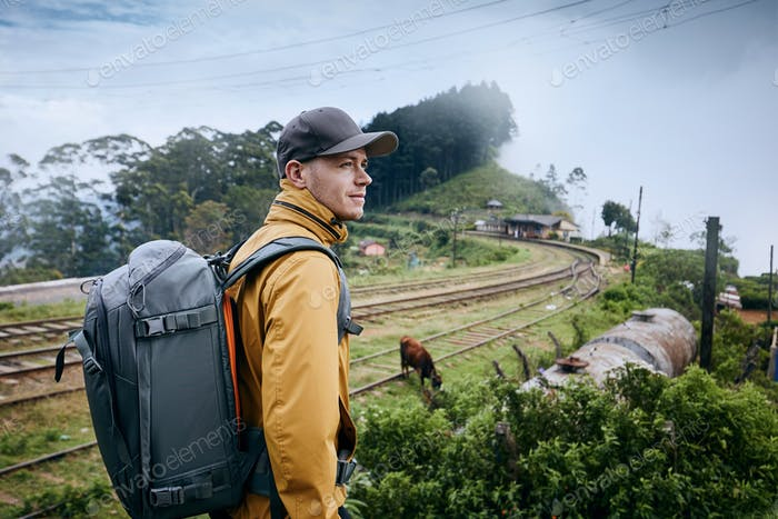 Portrait of young man with backpack against train station in clouds. Idalgashinna, Sri Lanka.