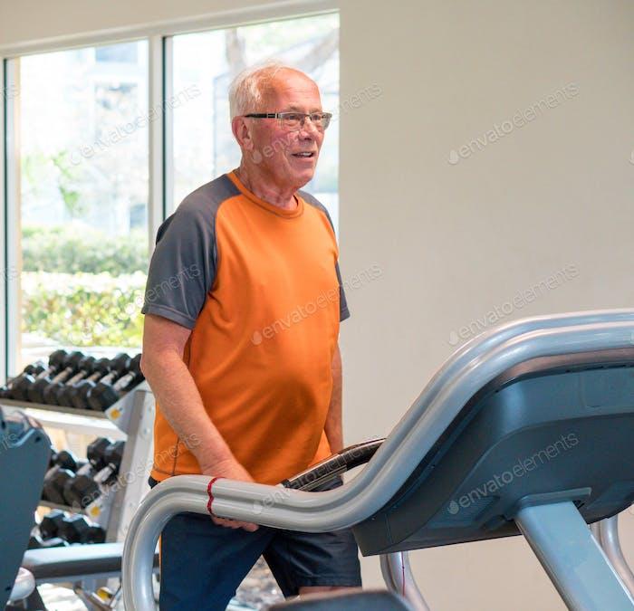 Active senior adult man on the treadmill