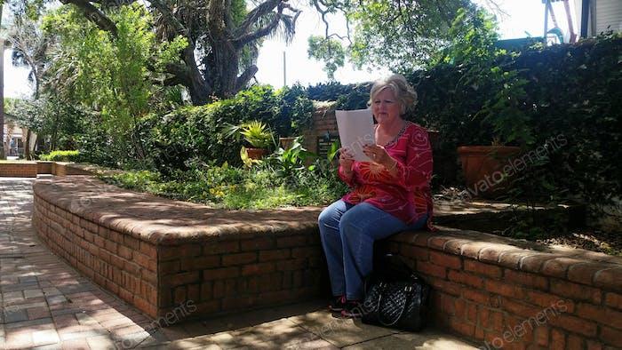 Frau mit Sehschwäche untersucht ihre Steuererklärung im kleinen Innenstadtpark...