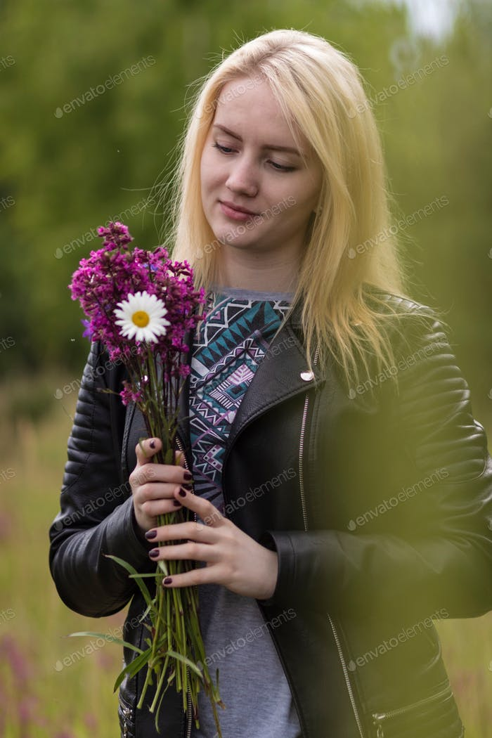 A young girl holds a bouquet of flowers in her hands