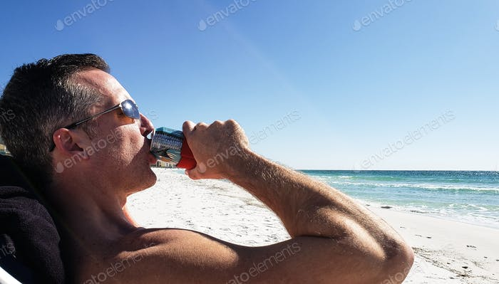 Millenial at the beach drinking his 5th beer while relaxing as a daily routine....