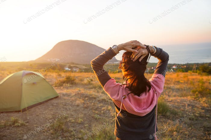 Woman meets the dawn in the mountains, rejoices in the sun. Panoramic view of the mountain and the s