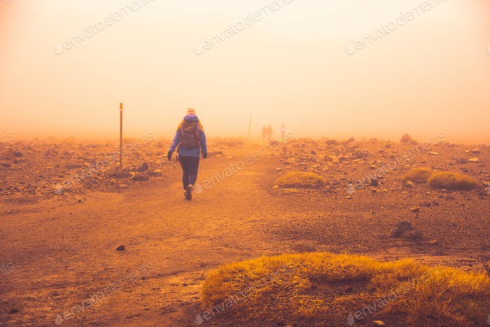 Woman hiking in new zealand in mordor during dust wind storm outdoors adventure