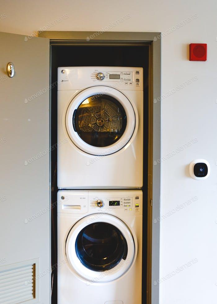 Apilado moderna lavadora y secadora en un armario en un apartamento