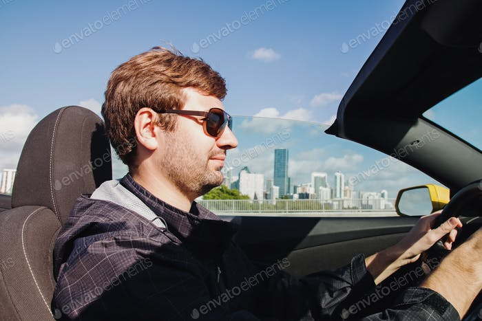 Young man in sunglasses driving cabriolet car