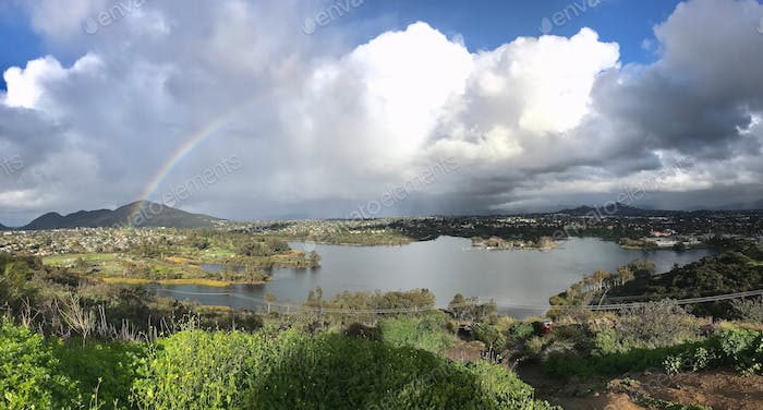 Rainbow 🌈 over the lake with sun and rain clouds and mountains. Precious resources. Nature love.