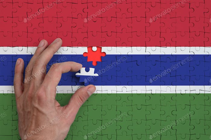 Gambia flag  is depicted on a puzzle, which the man's hand completes to fold.