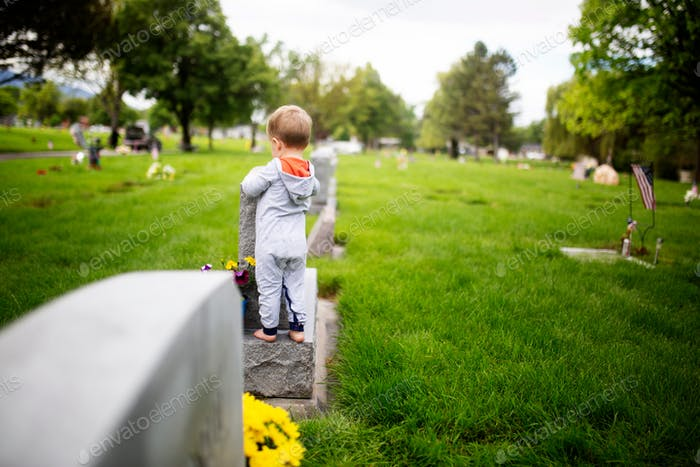 family cleaning gravestones at the cemetery