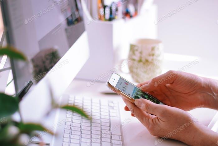Mujer sentada en un escritorio en la oficina en casa frente a una computadora y navegar Instagram en el teléfono móvil